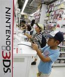 Мальчики играют в приставку Nintendo 3DS в магазине в Токио, 25 июля 2012 года. Квартальный убыток Nintendo Co Ltd, мирового лидера в производстве игровых консолей, оказался в два раза ниже того, что прогнозировали аналитики, благодаря сокращению расходов и новым программам. REUTERS/Yuriko Nakao
