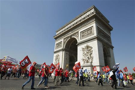 Employees of PSA Peugeot Citroen walk past the Arc de Triomphe in Paris July 25, 2012, as they demonstrate against the closure of the PSA Aulnay plant. PSA Peugeot Citroen vowed on Wednesday to press ahead with politically fraught restructuring plans as the troubled French automaker detailed mounting losses it has described as a threat to its future. Europe's second-largest car maker posted a 662 million-euro ($800 million) first-half auto-division loss that dragged its bottom line into the red - as it had warned earlier this month when announcing 8,000 French job cuts and a plant closure. REUTERS/Gonzalo Fuentes