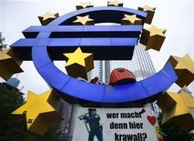 A demonstrator sits in the euro sculpture as the waits for police to clear the camp of occupy protestors in front of the European Central Bank (ECB) in Frankfurt, May 16, 2012. REUTERS/Kai Pfaffenbach