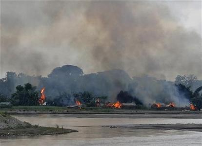 Flames erupt from huts built on the banks of river Gourang during violence near Kokrajhar town in the northeastern Indian state of Assam July 24, 2012. REUTERS/Stringer