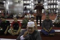 A man speaks into a microphone at Istiqlal mosque in Jakarta July 24, 2012.REUTERS/Beawiharta
