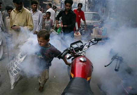 A boy tries to outrun a man fumigating for mosquitoes through the streets of Lahore in this September 20, 2011 file photo. REUTERS/Mohsin Raza/Files