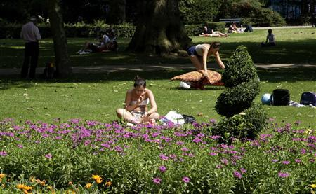 A woman reads a book in a garden on a sunny day in downtown London July 25, 2012. REUTERS/Max Rossi