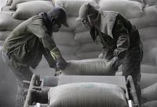 Рабочие перемещают мешки с цементом на заводе в китайском городе Хуайбэй, 17 марта 2010 года. Производство цемента в РФ в январе-июне 2012 года выросло на 14,5 процента до 27,7 миллиона тонн, что позволяет экспертам ожидать исторического рекорда по итогам года. REUTERS/Stringer