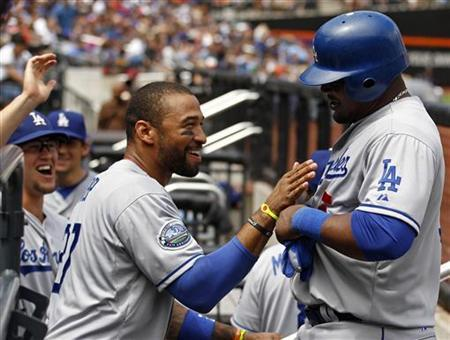 Los Angeles Dodgers Matt Kemp congratulates Juan Uribe after scoring on an RBI single by Dodgers Luis Cruz against the New York Mets during the third inning of their MLB National League baseball game at CitiField in New York, July 21, 2012. REUTERS/Adam Hunger