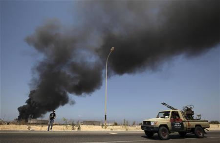 A Libyan rebel vehicle passes a liquefied petroleum gas tank as it burns outside the town of Brega, 240km (149 miles) southwest of the eastern city of Benghazi, August 28, 2011. REUTERS-Darrin Zammit Lupi