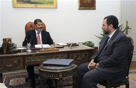 Egypt's President Mohamed Mursi (L) meets with Water Minister Hisham Kandil at the presidential palace in Cairo, July 22, 2012. Mursi has asked Kandil, a relatively young water minister little known outside Egypt, to form a new government, disappointing investors who had hoped for a high-profile economy specialist. Picture taken July 22, 2012. REUTERS/Egyptian Presidency/Handout