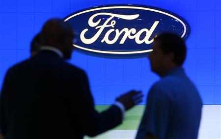 Men talk at the Ford exhibition as they attend the Washington Auto Show in this file photo taken January 27, 2012. REUTERS/Kevin Lamarque/Files