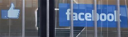The Facebook ''thumbs up'' icon and logo are displayed in a window at the offices of J.P. Morgan in New York City, New York, May 4, 2012. REUTERS/Lee Celano
