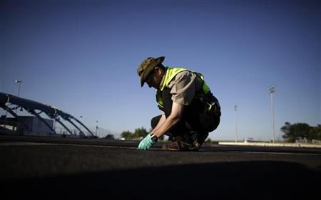 A member of an Israeli Rescue and Recovery team works at the site of the Wednesday bomb blast at the parking lot of Burgas Airport, some 400km (248miles) east of Sofia July 19, 2012. REUTERS/Stoyan Nenov
