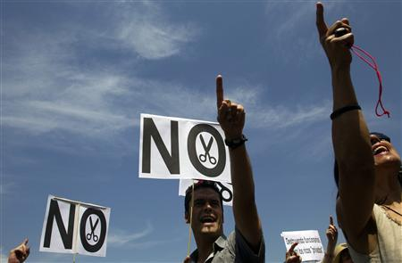 Civil servants hold ''No to cuts'' placards as they take part in a protest against government austerity measures outside Madrid's town hall July 25, 2012. REUTERS/Susana Vera