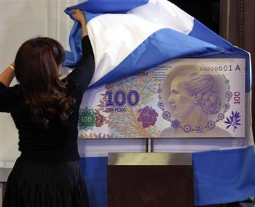 Argentina's President Cristina Fernandez de Kirchner unveils a large scale bill of the new 100 pesos bank note with a portrait of former First Lady Eva Peron to commemorate Thursday's 60th anniversary of Eva's death, during a ceremony at the Casa Rosada Presidential Palace in Buenos Aires July 25, 2012. REUTERS/Marcos Brindicci