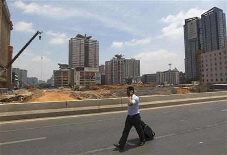 A man walks past a residential construction site with his luggage as he speaks on a mobile phone in Changsha, Hunan province July 9, 2012. REUTERS/Stringer