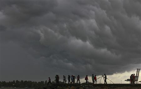 People stand on a seaside promenade against the background of pre-monsoon clouds gathered over the Arabian Sea at Kochi in the southern Indian state of Kerala in this June 4, 2012 file photo. REUTERS/Sivaram V/Files
