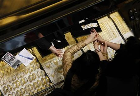 Customers try 24K gold bracelets a Chow Tai Fook Jewellery store in Hong Kong December 6, 2011. REUTERS/Bobby Yip/Files