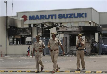 Police officials walk outside the Maruti Suzuki's plant in Manesar, located in Haryana, July 19, 2012. REUTERS/Ahmad Masood