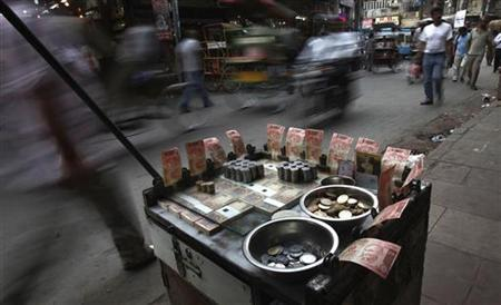 People walk past a roadside currency exchange vendor in the old quarters of Delhi May 22, 2012. REUTERS/Adnan Abidi/Files