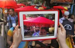 A participant uses an iPad to take pictures of a rally as part of the week-long sex workers' freedom festival at the Sonagachi red-light area in Kolkata July 24, 2012. REUTERS/Rupak De Chowdhuri