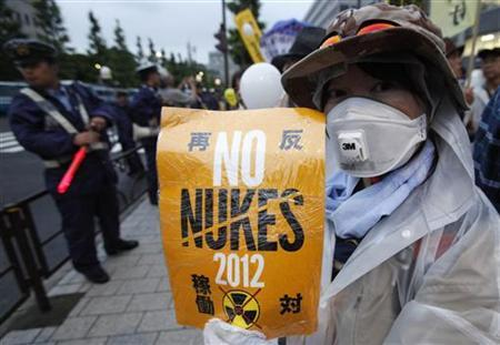 A woman wearing a mask takes part in an anti-nuclear demonstration outside prime minister's official residence in Tokyo July 20, 2012. REUTERS/Yuriko Nakao