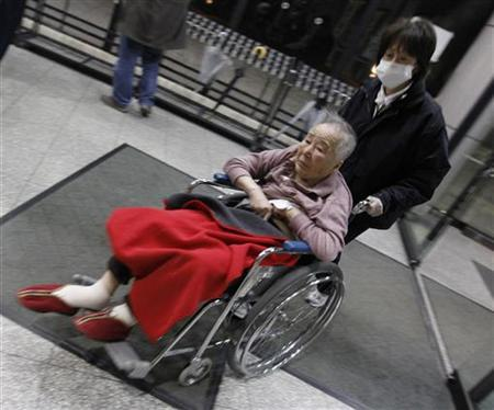 A caretaker helps a woman, evacuated from a nursing home, to a temporary shelter after radiation leaked from an earthquake-damaged Fukushima nuclear reactor, in Koriyama, northeastern Japan March 12, 2011. REUTERS/Jo Yong-Hak