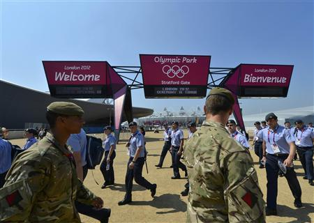 Military personnel walk past a welcome sign to Olympic Park before the start of the London 2012 Olympic Games July 26, 2012. REUTERS/Toby Melville