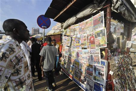 People read newspapers reporting the death of Ghana's President John Atta Mills on Tuesday, in the capital Accra, July 26, 2012. REUTERS/Yaw Bibini
