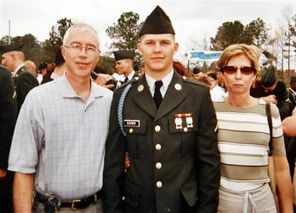 Army veteran Michael Ecker is pictured with his parents Matt and Cheryl at his graduation from boot camp in this photo shown in Champion, Ohio, April 19, 2012. On a warm summer afternoon in Champion, Michael Ecker, a 25-year-old Iraq war veteran, called out to his father from a leafy spot in their backyard. Then, as the two stood just steps apart, Michael saluted, raised a gun to his head and pulled the trigger. REUTERS-Jason Cohn