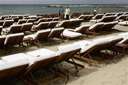 Tourists walk along Banus beach in Marbella, on the Costa del Sol, May 24, 2007. REUTERS/Jon Nazca