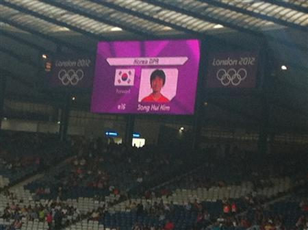 The South Korea flag is displayed beside North Korea soccer player Song Hui Kim before the start of the women's Olympic soccer match between North Korea and Colombia at the London 2012 Olympic Games in Hampden Park, Glasgow, Scotland July 25, 2012. REUTERS/James Crossan/Handout