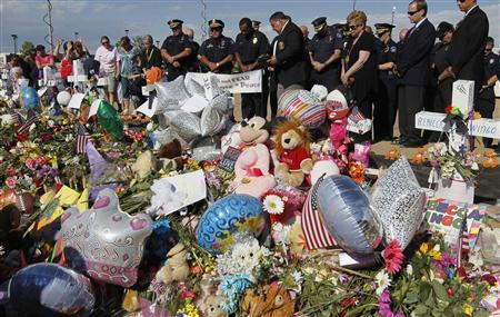 Aurora Colorado firefighters and police pray at the memorial for victims of the movie theater shooting in Aurora July 25, 2012. REUTERS/Rick Wilking