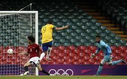 O brasileiro Leandro Damião (centro) marca um gol entre o jogador egípcio Mahmoud Alaa Eldin e o goleiro Ahmed Elshenawi (direita) durante uma partida dos Jogos Olímpicos de Londres no Millennium Stadium em Cardiff, na Escócia. 26/07/2012 REUTERS/François Lenoir