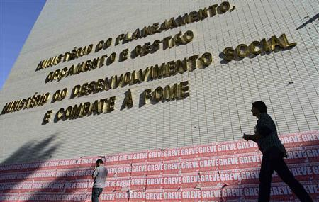 People walk past banners hanging on the facade of the Brazil's Ministery of Planning, Budget, & Management in Brasilia July 25, 2012. REUTERS/Cadu Gomes