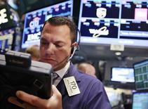Трейдер на Нью-Йоркской фондовой бирже, 24 июля 2012 года. Американские акции выросли в четверг, вдохновившись комментариями главы Европейского центробанка и проигнорировав смешанные корпоративные результаты. REUTERS/Brendan McDermid