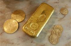 Золотой слиток и монеты в обменной кассе в Ницце, 8 октября 2008 года. Золотодобывающая компания Newmont Mining Corp снизила прибыль на 30 процентов во втором квартале за счет сокращения производства золота и меди и сократила прогноз добычи на 2012 год. REUTERS/Eric Gaillard
