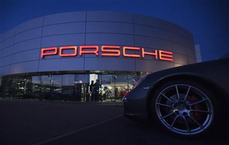 An illuminated Porsche logo is pictured on a building of a Porsche retail centre in Niederwangen, outside Bern March 9, 2012. REUTERS/Michael Buholzer