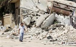 A Syrian civilian walks along a destroyed street in Azaz, northern Syria, July 25, 2012. REUTERS/Umit Bektas