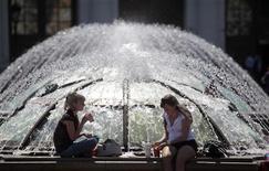 Девушки обедают, сидя на фонтане в центре Москвы, 7 июня 2011 года. Наступающие выходные в Москве будут жаркими, прогнозируют синоптики. REUTERS/Alexander Natruskin