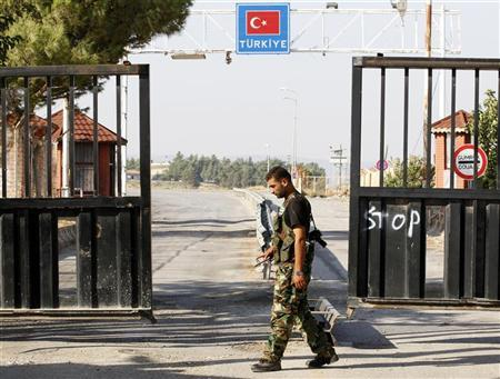 A Free Syrian Army soldier mans the last gate before the Turkish territory at the Bab Al-Salam border crossing July 22, 2012. REUTERS/Umit Bektas