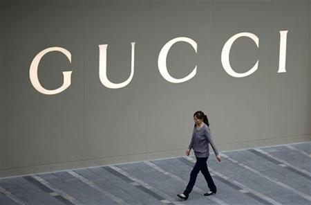 A woman walks by a Gucci luxury boutique at the IFC Mall in Shanghai June 4, 2012. REUTERS/Carlos Barria