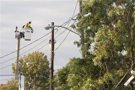 A utility worker repairs damage to power lines the morning after the town was hit by a tornado in Elmira, New York July 27, 2012. REUTERS/Adam Fenster