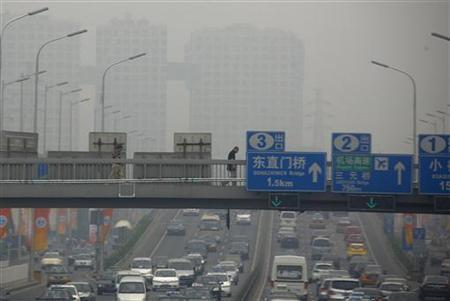A pedestrian walks across a bridge above a main road on a day with high air pollution in Beijing June 6, 2012. REUTERS/David Gray