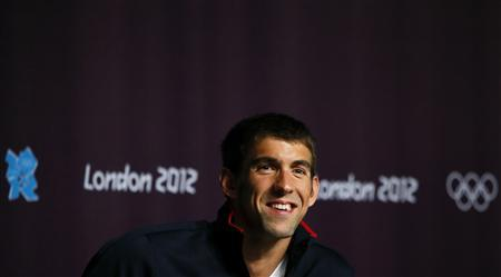 Michael Phelps of the U.S. smiles as he listens to reporter's questions during a news conference in the Olympic media centre before the start of the London 2012 Olympic games July 26, 2012. REUTERS/Kai Pfaffenbach
