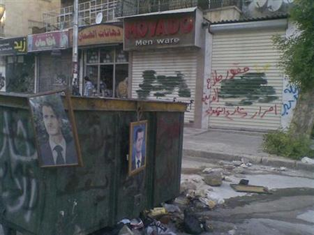 Pictures of Syria's President Bashar al-Assad hang from garbage containers in Aleppo July 24, 2012. Picture taken July 24, 2012. REUTERS/Shaam News Network/Handout
