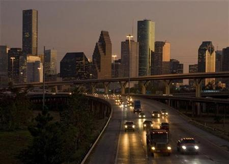 Traffic flows at dusk with the downtown Houston skyline in the background as night falls. October 3, 2008.