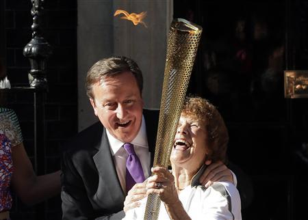 Britain's Prime Minister David Cameron (L) greets Olympic torch bearer Florence Rowe (R) after she received the flame in Downing Street in London July 26, 2012. REUTERS/Cathal McNaughton