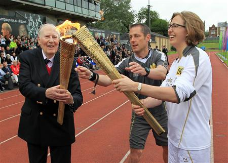 Roger Bannister (L) passes the Olympic flame to torchbearer Nicola Byrom during the London 2012 Olympic Games torch relay at the Iffley Road Stadium in Oxford, southern England in a July 10, 2012 file photo. REUTERS/LOCOG/Pool/files