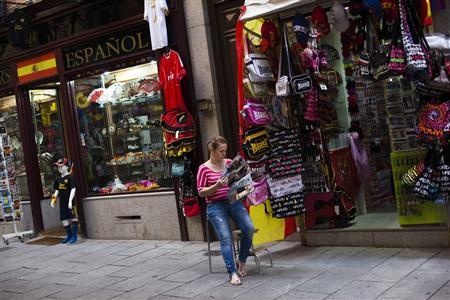 A shop assistant waits for customers while reading a magazine outside a souvenir store in Madrid July 27, 2012. Spain has for the first time conceded it might need a full EU/IMF bailout worth 300 billion euros ($366 billion) if its borrowing costs remain unsustainably high, a euro zone official said. REUTERS/Susana Vera