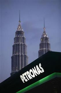 Malaysia's Petronas Twin Towers are pictured in the background as a Petronas logo is seen on the roof of its natural gas station in Kuala Lumpur February 4, 2012. REUTERS/Bazuki Muhammad