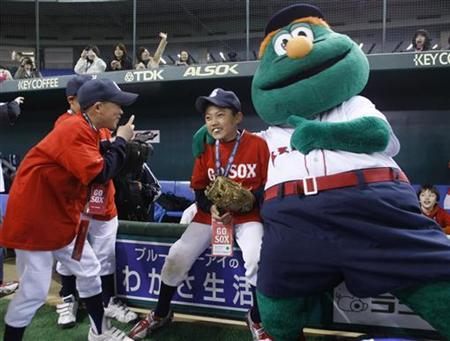 Children play with Wally, the mascot of the Boston Red Sox, before a baseball clinic organised by the Red Sox in Tokyo March 24, 2008. REUTERS/Kim Kyung-Hoon