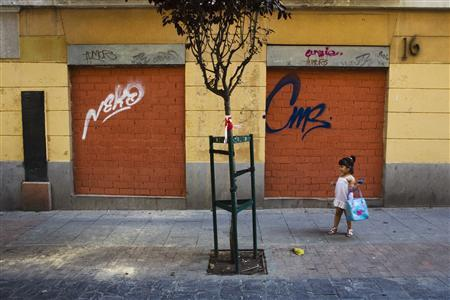 A girl stands next to a closed down business in Madrid July 27, 2012. Spain has for the first time conceded it might need a full EU/IMF bailout worth 300 billion euros ($366 billion) if its borrowing costs remain unsustainably high, a euro zone official said. REUTERS/Susana Vera